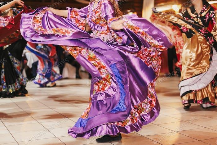 Schöne Zigeunermädchen tanzen in traditionellem Blumenkleid