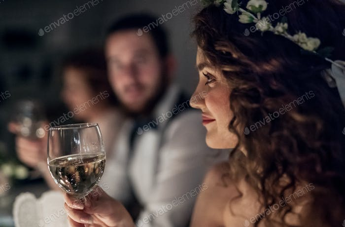 A close-up of a young bride sitting at a table on a wedding, holding a glass of wine.