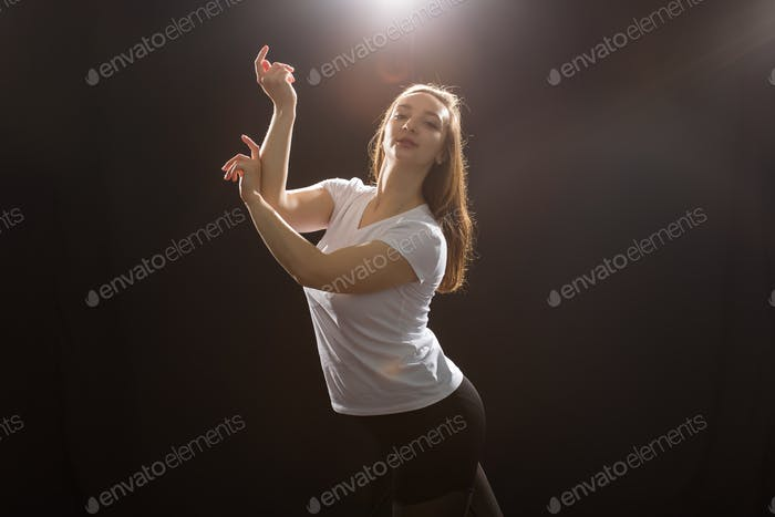 People and dancing concept - Young beautiful sporty woman dancing jazz funk on a black studio