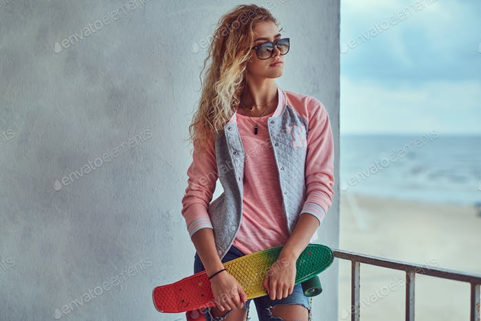 Portrait of a happy charming young girl with blonde hair holds a skateboard outdoors
