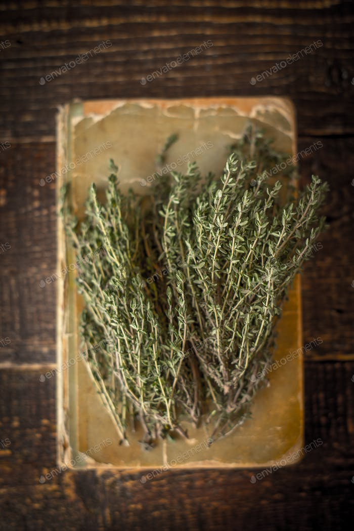 Old cook book with thyme on the wooden table vertical