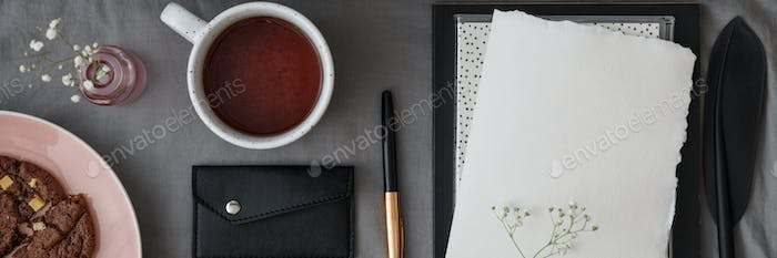 Top view of a lunch break arrangement with a cup of tea, pen and