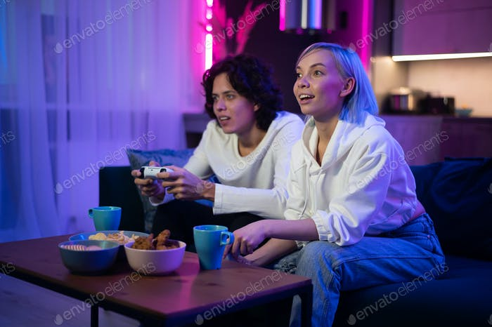 Couple playing videogame on console. Girl losing and not letting the guy play normally by closing