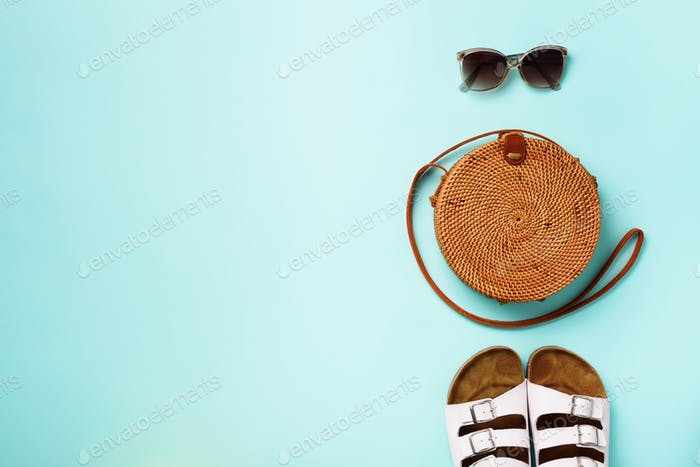 Stylish rattan bag, birkenstocks, sunglasses on blue background. Top view with copy space. Trendy