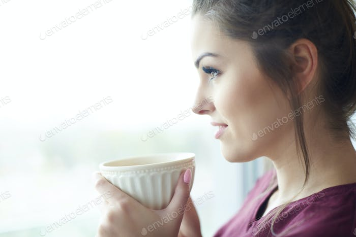 Headshot of attractive woman having morning coffee