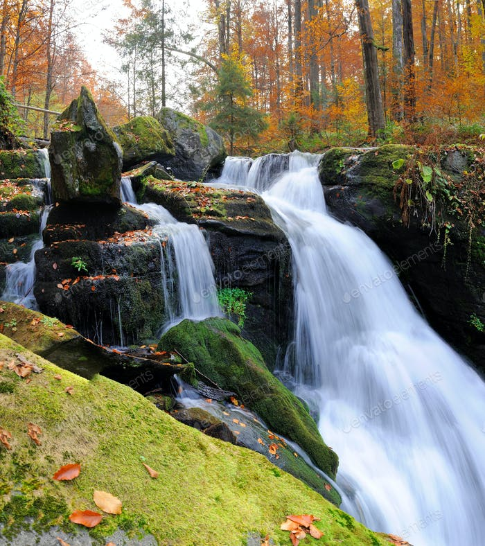 Mountain waterfall in autumn forest