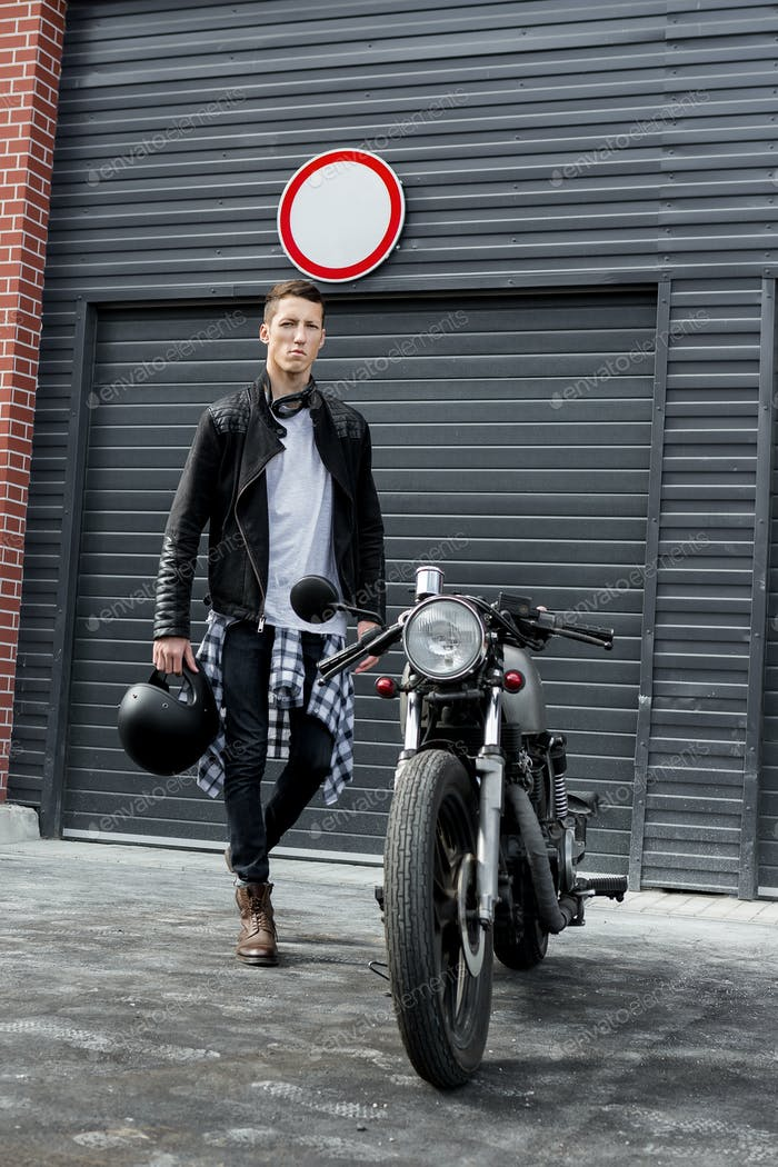 Brutal Mann in der Nähe seines Cafe Racer Custom Motorrad.