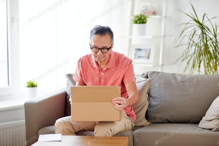 man opening parcel box at home