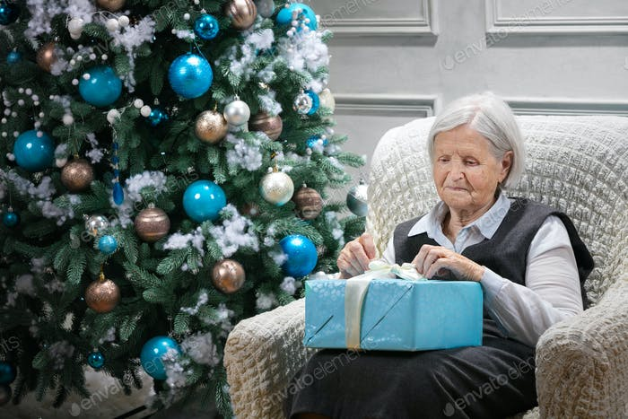 Senior woman opening a package with a gift while sitting beside a Christmas tree