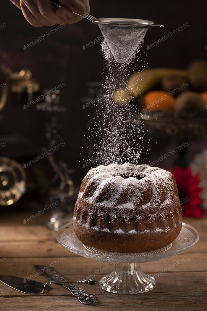 Banana cake on a wooden table and throwing sugar powder on it