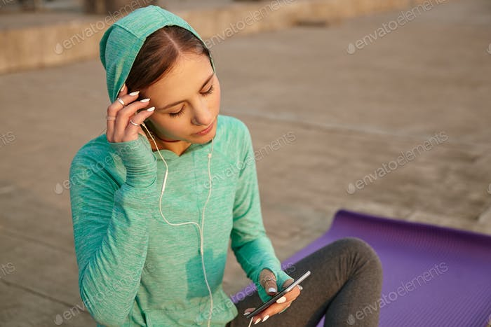 Sporty young lady wears sportswear, morning stretching on purple yoga mat, trains at the seaside