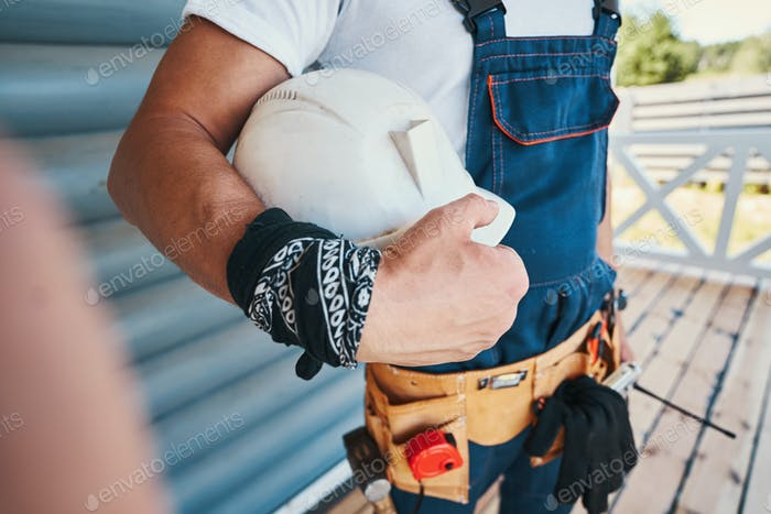 Construction worker keeping safety helmet in right hand