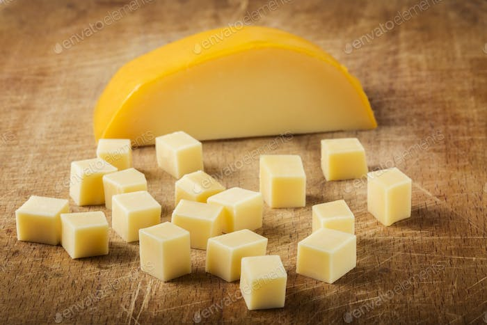 Cubes of yellow cheese stacked randomly