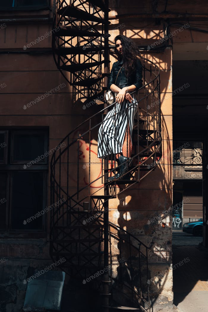 Girl posing on a spiral staircase