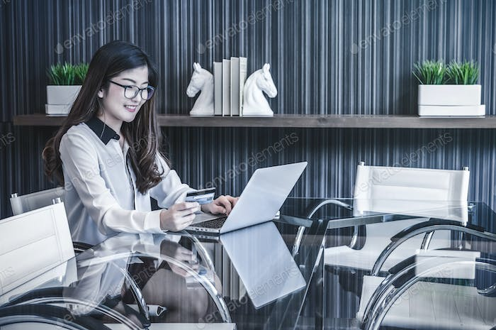 Portrait of smiling asian beautiful young businesswoman sitting at workplace