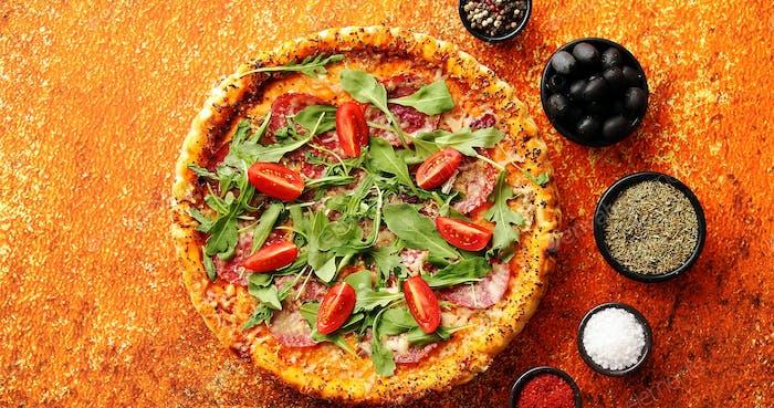Leckere Pizza auf rostigen Hintergrund mit Gewürzen, Kräutern und Gemüse