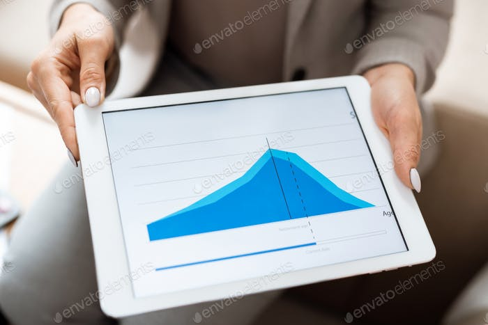 Hands of real estate agent holding tablet with blue financial graph on display