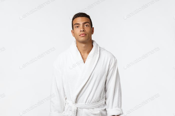 African American guy wearing a bathrobe with happy emotion. Isolated over whtie background