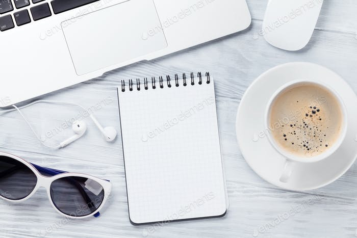 Desk table with laptop, coffee, notepad and sunglasses