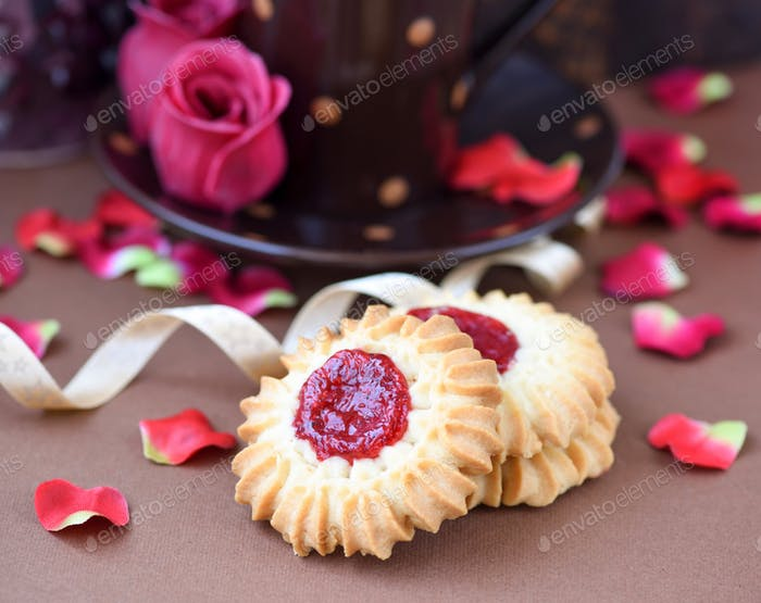 Shortbread cookies with jam in the middle on plate against brown