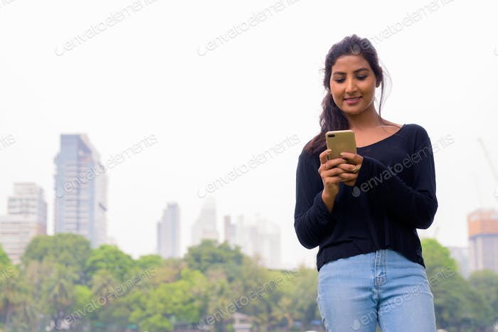 Happy young beautiful Persian woman using phone at the park