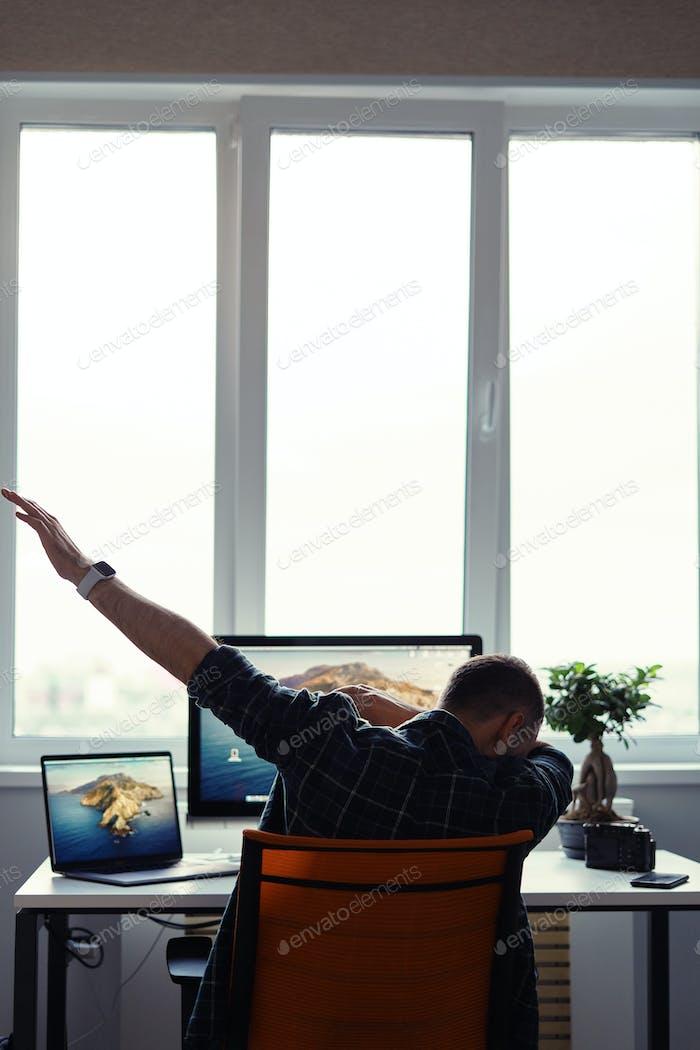 Победоносный человек празднует свой успех на рабочем месте