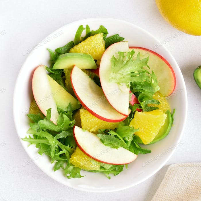 Fruit vegetable salad with red apples, avocado, orange slices
