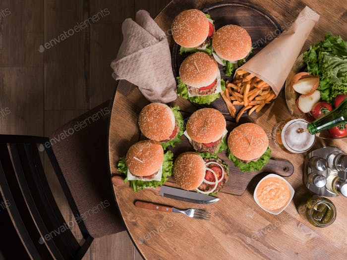 Top view of different tasty burgers with vegetables