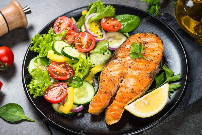 Grilled salmon fish steak with vegetables on black