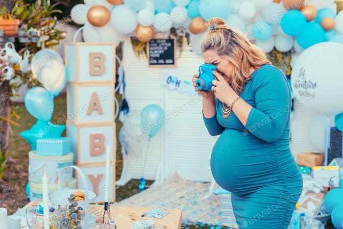 Pregnant woman taking photos of a decorated table for baby shower
