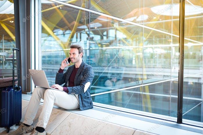 Mann sitzt am Flughafen mit Laptop und Handy neben