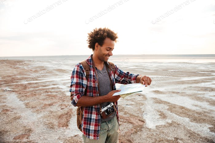 Cheerful man with backpack standing and examening map outdoors