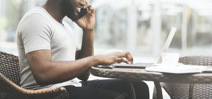 Unrecognizable african man talking by phone while working