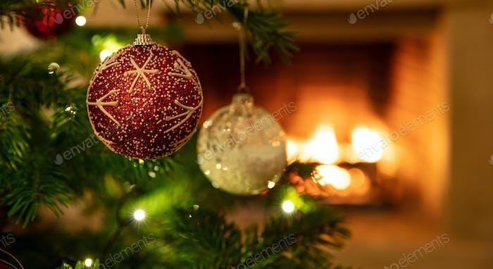 Christmas tree close up on burning fireplace background