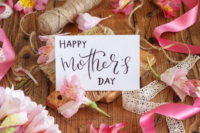Happy Mother's Day card on a wooden table between pink flowers