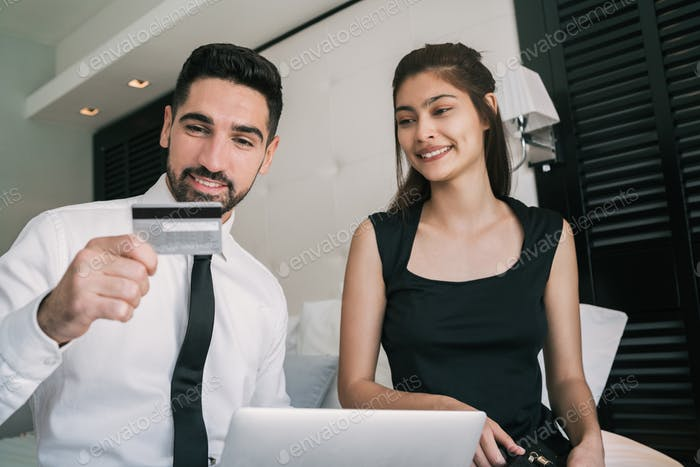 Two business people using credit card for online payment.