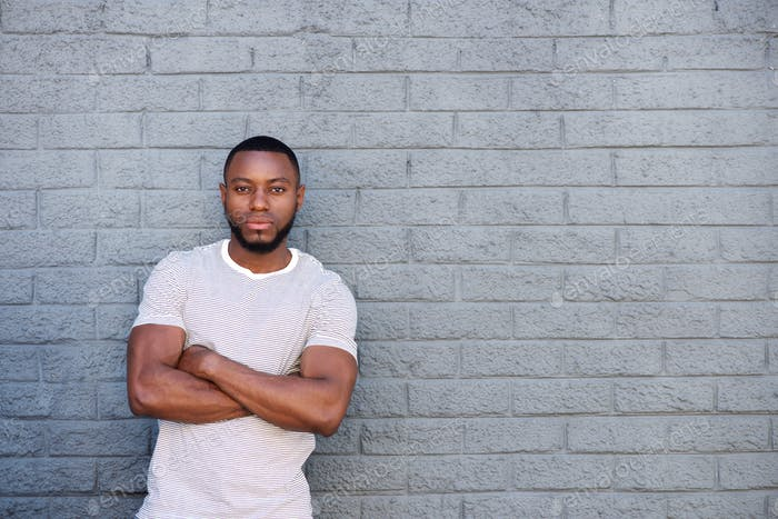 ernsthafte muskulöse Mann stehend durch Ziegelmauer außerhalb