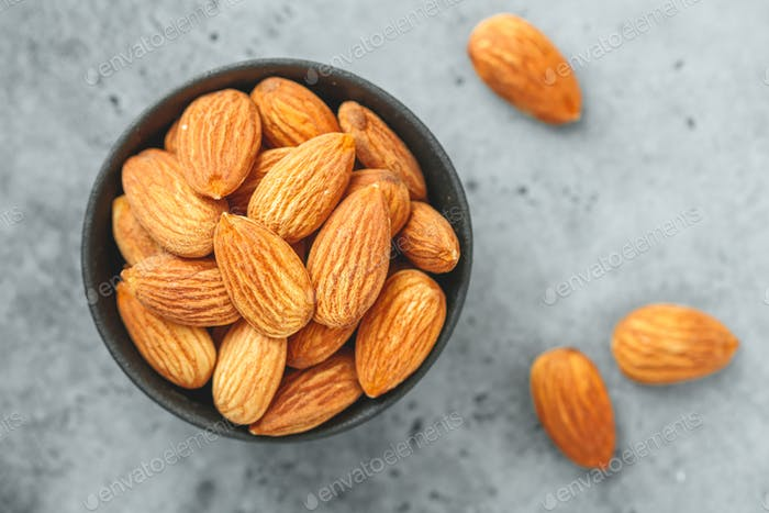 Fresh almond nuts in a back bowl on a textured grey table. Top view.