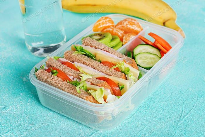 Schule Lunchbox mit Sandwich, Gemüse, Wasser und Obst auf dem Tisch.