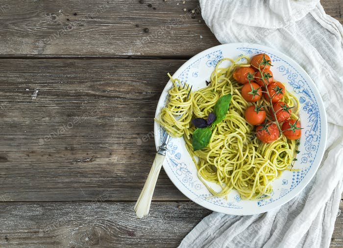 Pasta spaghetti with pesto sauce, basil, baked cherry-tomatoes