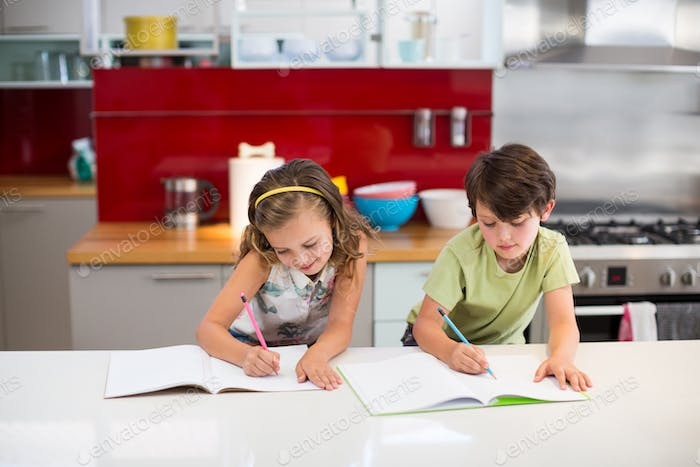 Siblings doing homework in kitchen