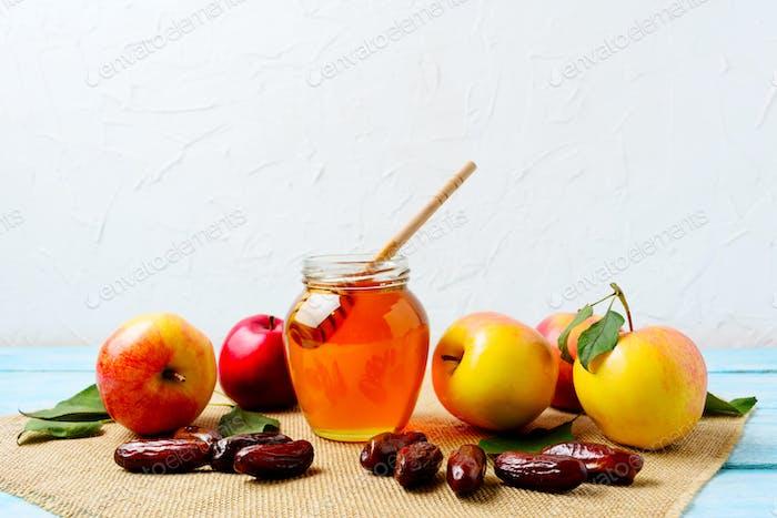 Honey jar, dates and ripe apples on burlap napkin