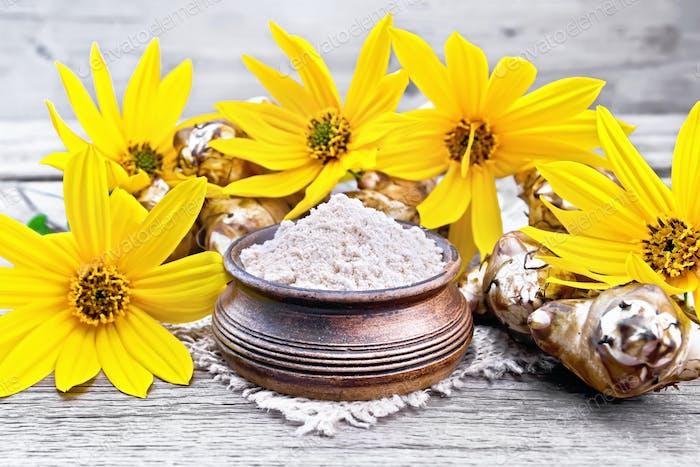 Flour of Jerusalem artichoke in bowl on board