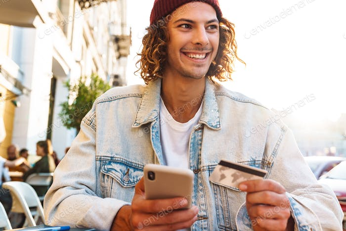 Man sitting in cafe while holding credit card