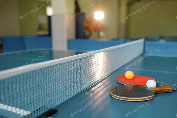 Ping pong rackets and balls on game table with net