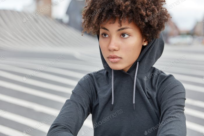 Cropped view of thoughtful dark skinned young sportswoman in stylish hoodie, focused into distance,