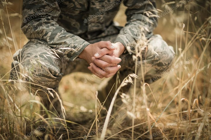 Military soldier crouching in grass