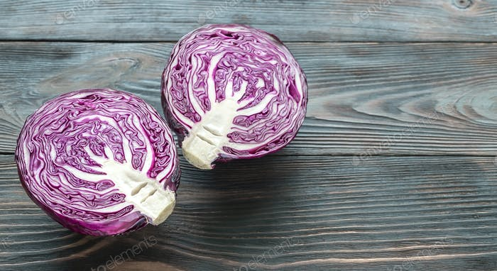 Halved red cabbage on the wooden background