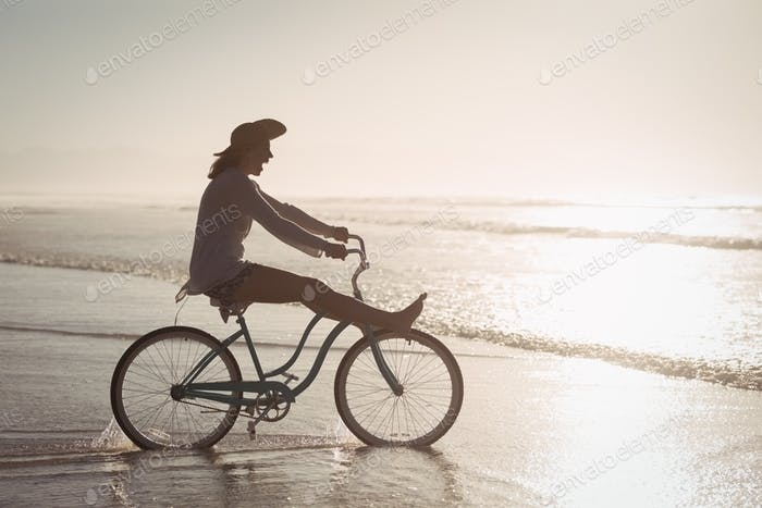 Side view of cheerful woman riding bicycle on shore at beach