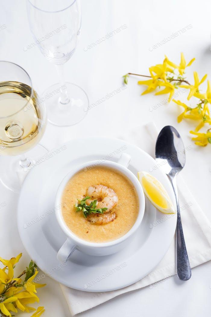 Cremige Suppe mit Meeresfrüchten und Zitrone auf weißem Hintergrund.